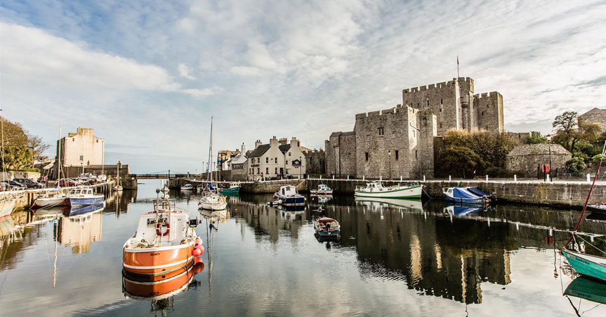 photo shows castle rushen on the isle of man with boats in the foreground